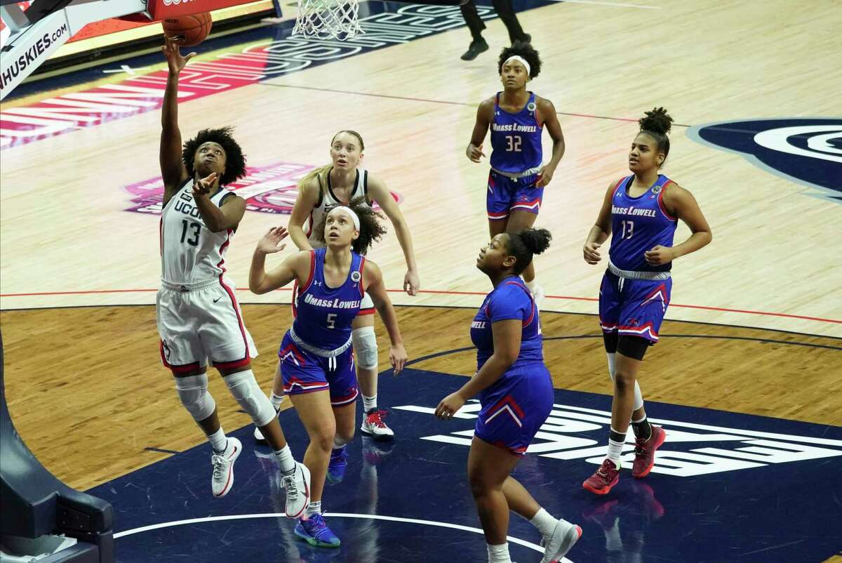Connecticut guard Christyn Williams (13) shoots past UMass-Lowell guard Kharis Idom (5) during the first half of an NCAA college basketball game, Saturday, Dec. 12, 2020, in Storrs, Conn. (David Butler II/Pool Photo via AP)