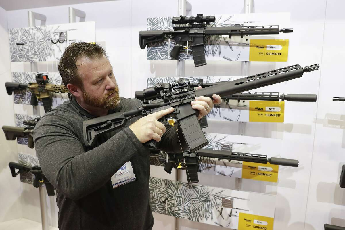 FILE - Bryan Oberc, Munster, Ind., tries out an AR-15 from Sig Sauer in the exhibition hall at the National Rifle Association Annual Meeting in Indianapolis, Saturday, April 27, 2019.