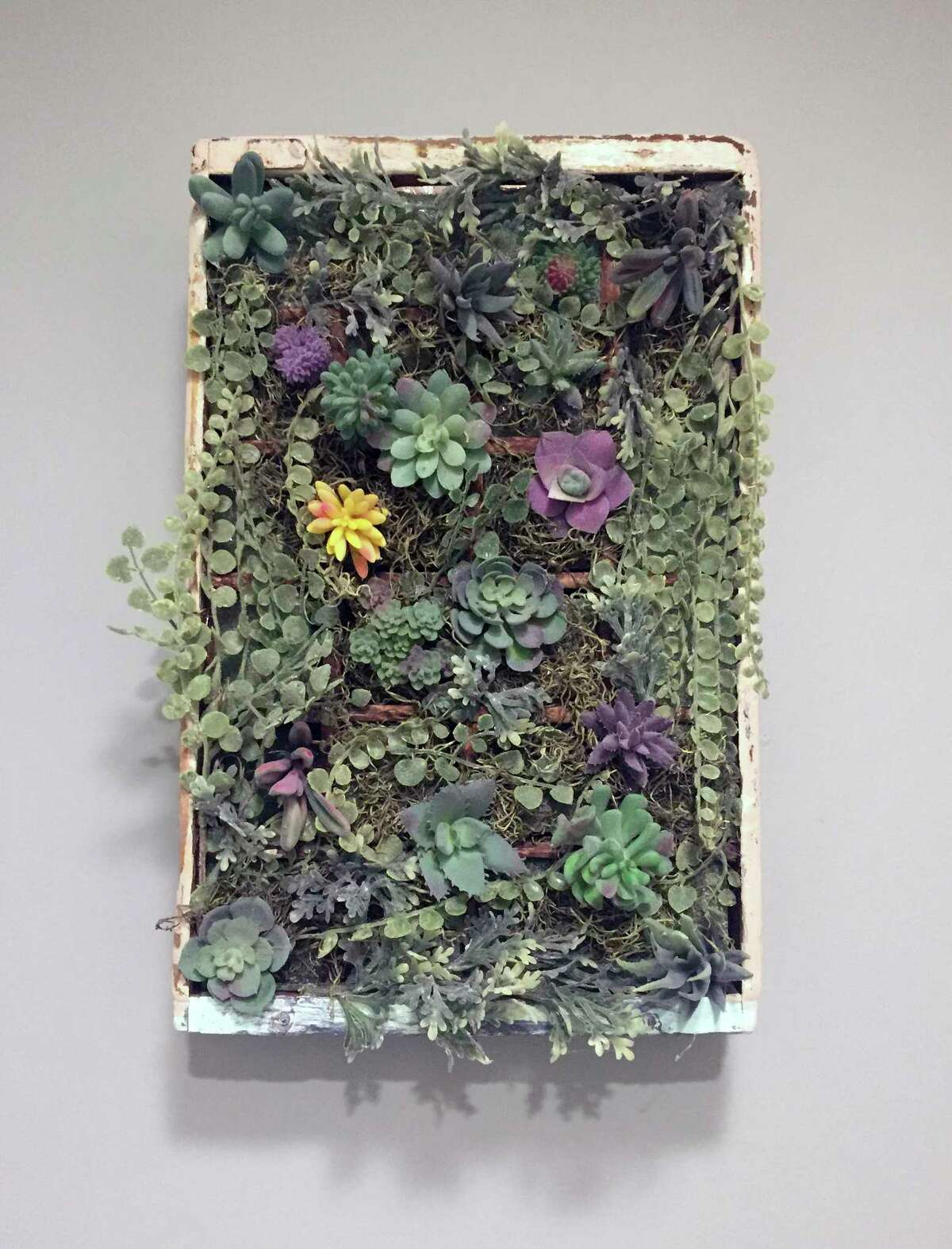 """Ashley Martin, a teacher and part time crafter in Green Township, N.J., created this display out of a scrounged wooden soda bottle crate and a collection of succulents. Martin says she's always loved doing arts and crafts projects, but she really became obsessed with cottagecore décor when she and her husband bought an 1850s farmhouse. Turning her ideas into custom art and signs became a side gig for her, and she's busy working on orders for the holidays now. I really enjoy working on something creative any time that I can. For me, it's an outlet."""" (Ashely Martin via AP)"""