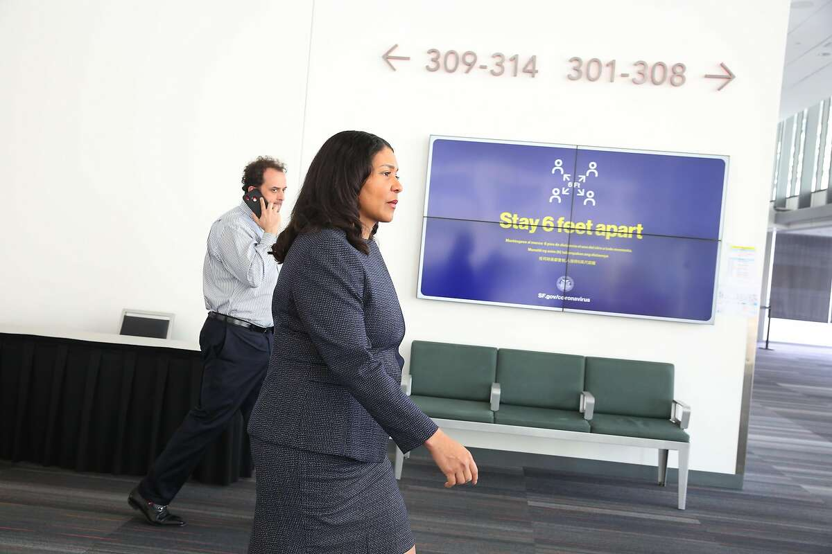 Mayor London Breed (front) and chief of staff Sean Elsbernd staff walk past a social-distancing reminder March 27 as they walk through the Emergency Operations Center at Moscone Center in San Francisco.