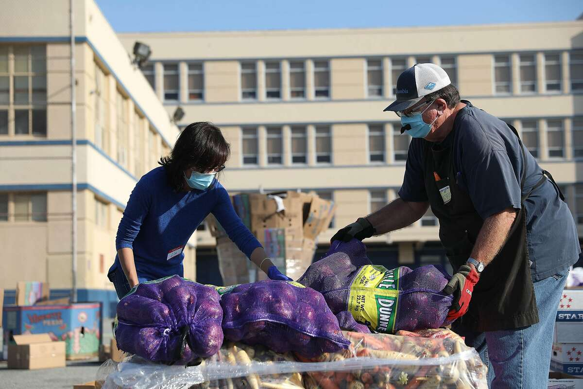 Volunteers Lin Mai (l to r) and Dave Gilliam work together moving sacks of onions as they work at the San Francisco-Marin Food Bank pop-up food pantry at Denman Middle School on Wednesday, October 28, 2020 in San Francisco, Calif.