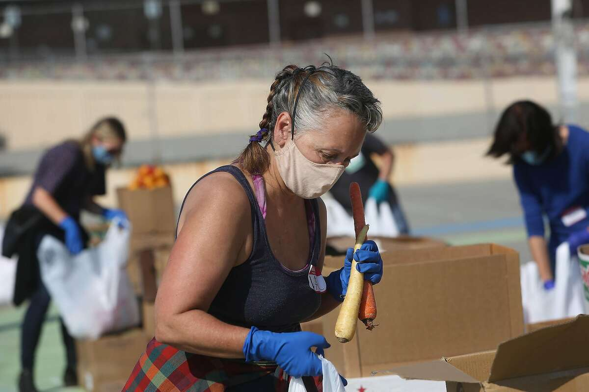Valerie Fa�hman, loads a bag with produce while volunteering at the San Francisco-Marin Food Bank pop-up food pantry at Denman Middle School on Wednesday, October 28, 2020 in San Francisco, Calif.