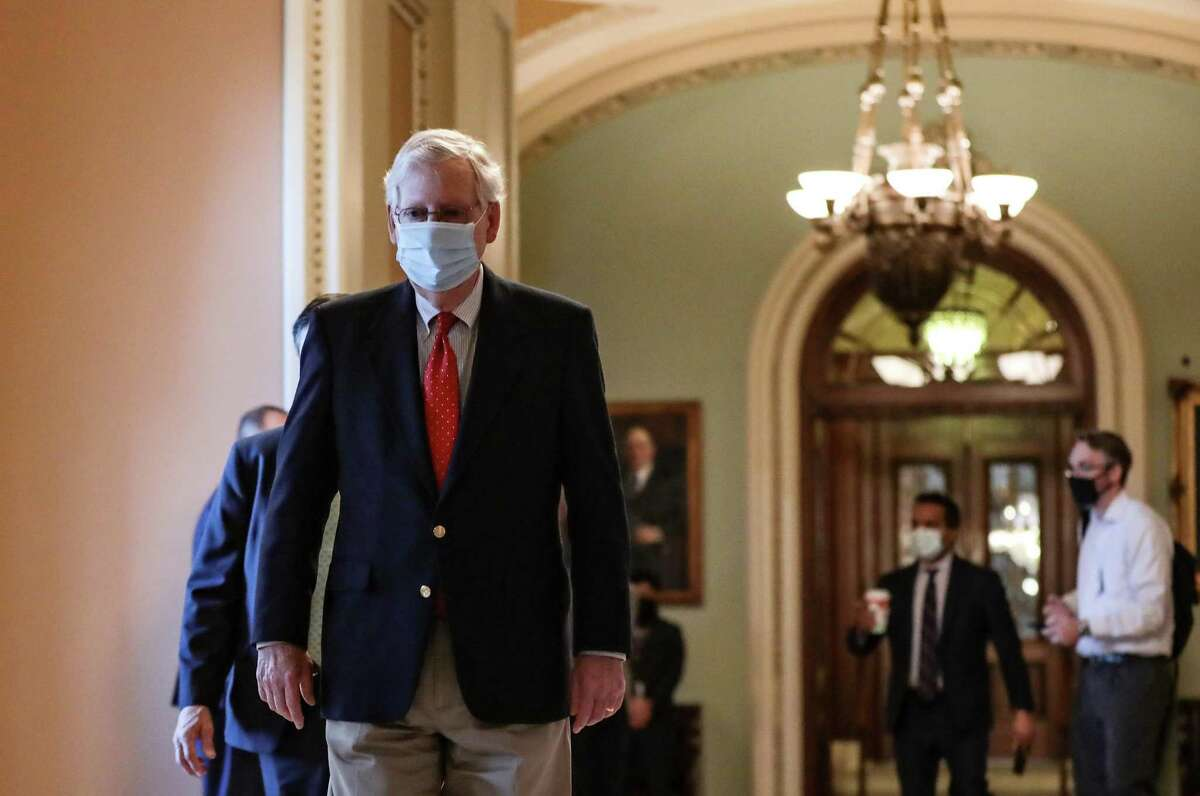 Senate Majority Leader Mitch McConnell walks from the Senate floor to his office at the U.S. Capitol in Washington, D.C., U.S., on Dec. 11. Bipartisan talks on a nearly trillion-dollar pandemic relief bill in Congress are hung up on differences between Republicans and Democrats on shielding companies from virus-related lawsuits, raising doubts about a deal.
