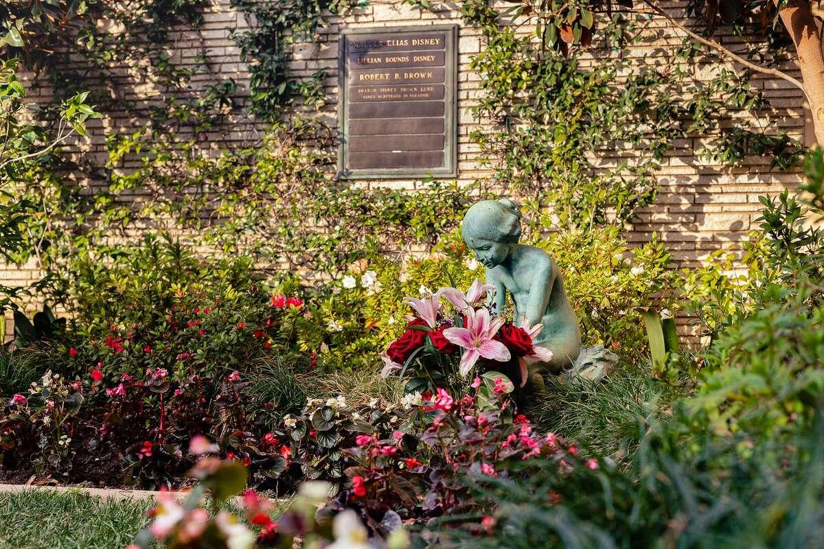 Flowers left by the Little Mermaid statue in Disney's memorial garden