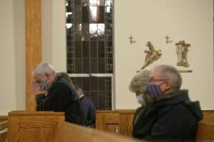 Attendees read, reflected or prayed in silence before the first mass of the day at St. Rose of Lima Church on the eighth anniversary of the Sandy Hook shooting Monday in Newtown. See more photos on A9.
