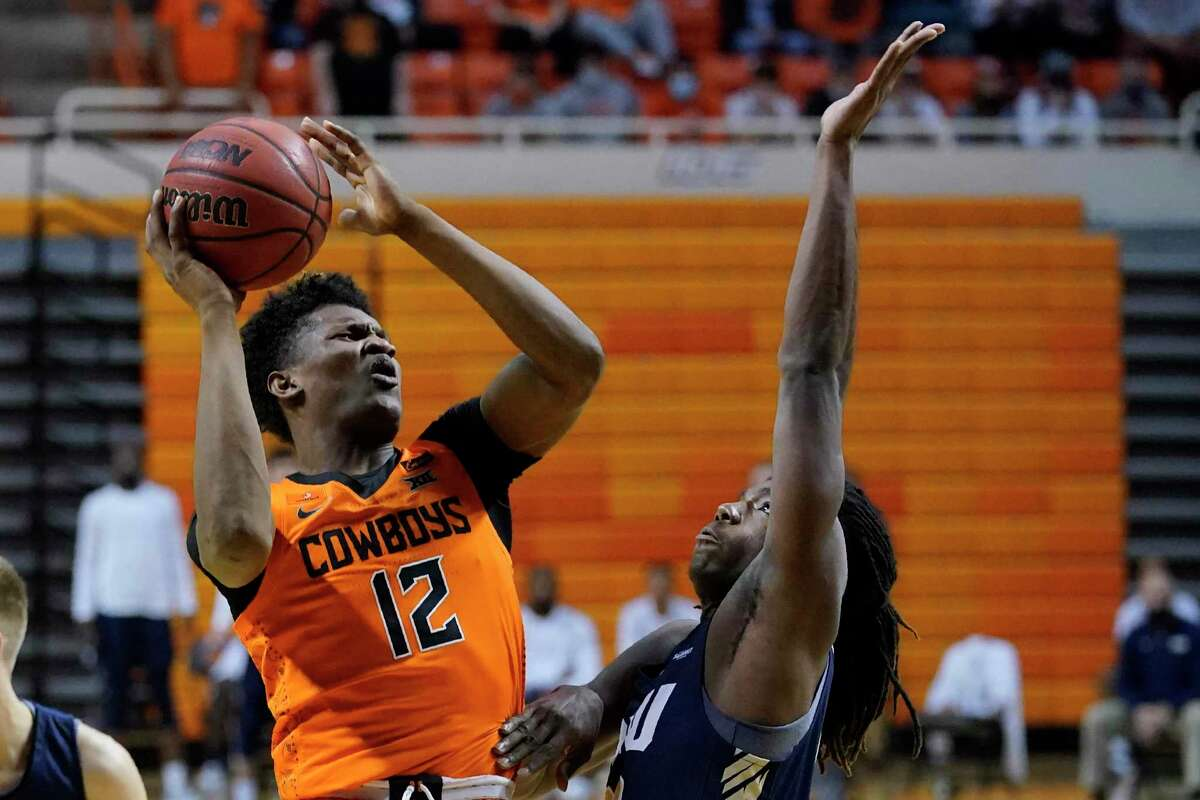 Oklahoma State forward Matthew-Alexander Moncrieffe (12) shoots in front of Oral Roberts center Nate Clover III during the second half of an NCAA college basketball game Tuesday, Dec. 8, 2020, in Stillwater, Okla. (AP Photo/Sue Ogrocki)