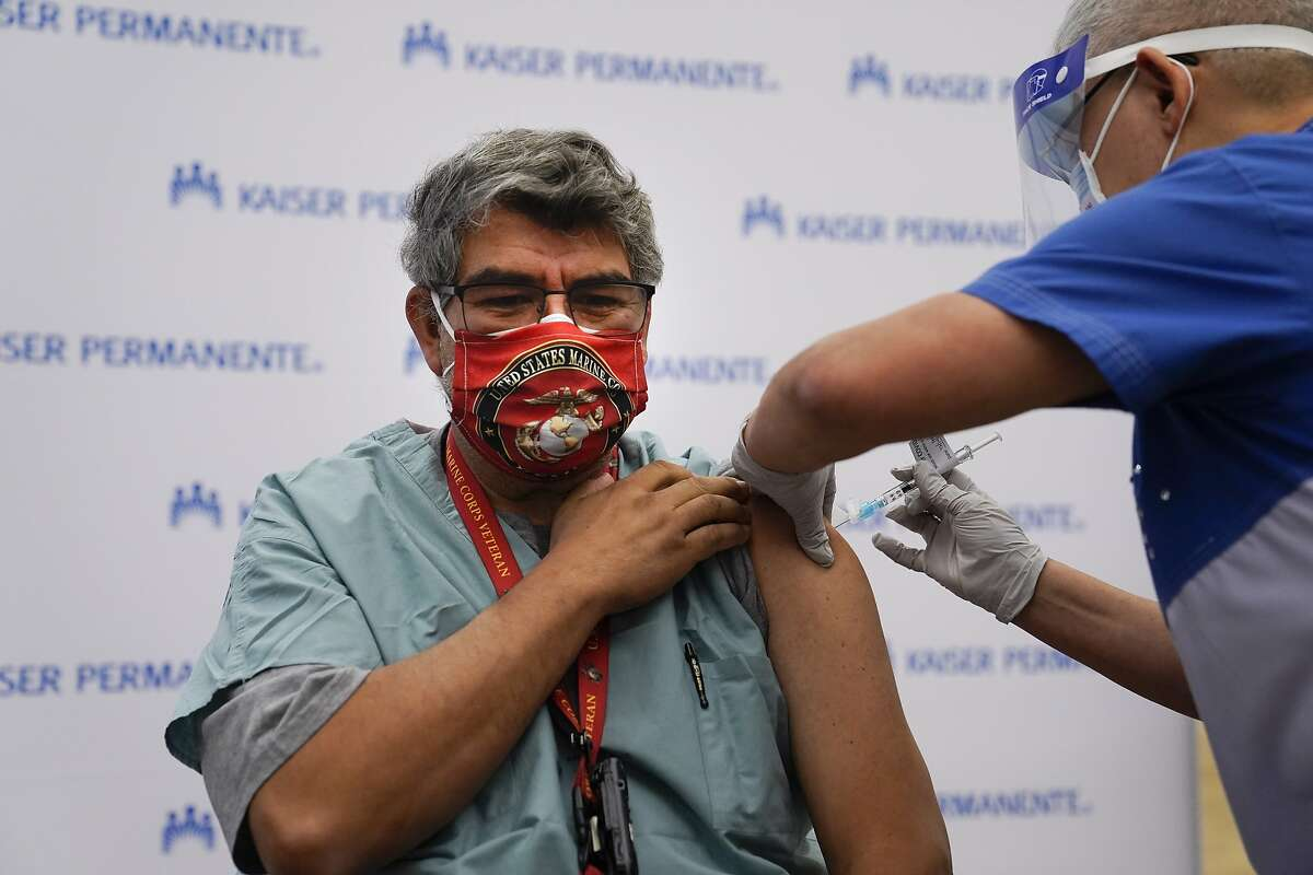 Respiratory care practitioner Raul Aguilar receives the Pfizer-BioNTech COVID-19 vaccine at Kaiser Permanente Los Angeles Medical Center in Los Angeles, Monday.