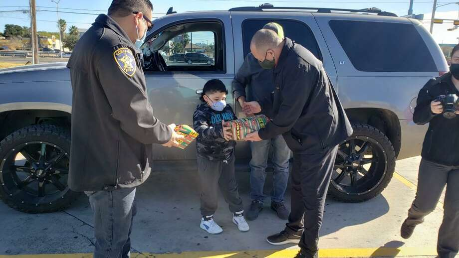 Precinct 2 Constable Mike Villarreal and Precinct 2 Place 1 Justice of the Peace Bobby Quintana surprised motorists in south Laredo with Christmas gifts for their children instead of citations. Photo: César G. Rodriguez /Laredo Morning Times