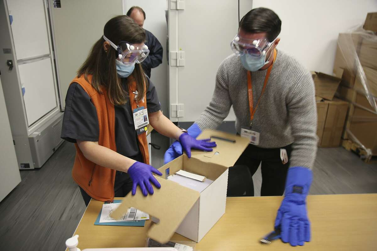 Jennifer Harrison, senior director of clinical operations at the University of Texas Health Austin Dell Medical School, and Devin Kline, materials manager open the first shipment of Pfizer-BioNTech COVID-19 vaccines to arrive at the hospital in Austin, Texas on Monday Dec.14, 2020. The facility received almost 3,000 doses and was among the first four hospitals in Texas to receive a shipment. (AP Photo/John L. Mone)