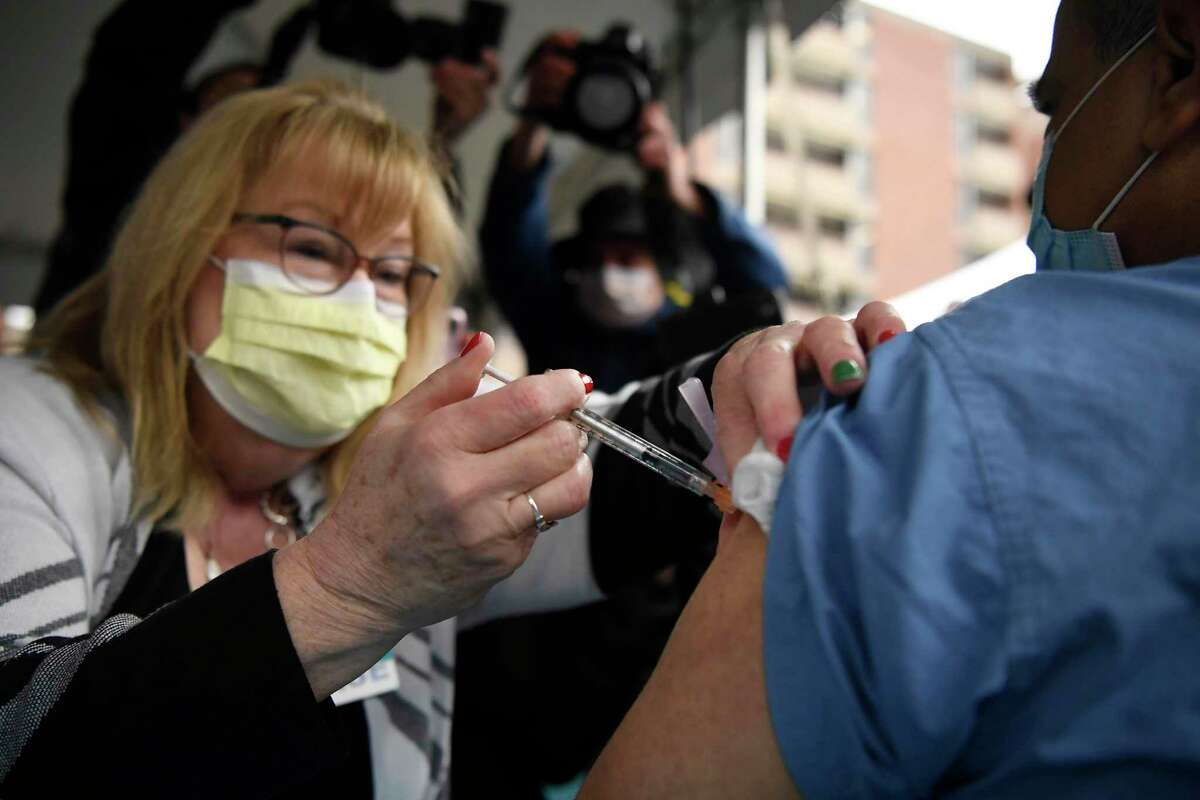 Nurse Marylou Oshana administers the Pfizer-BioNTech vaccine for COVID-19 to Dr. Ajay Kumar, executive vice president and chief clinical officer for Hartford HealthCare, outside Hartford Hospital, Monday, Dec. 14, 2020, in Hartford, Conn. (AP Photo/Jessica Hill)