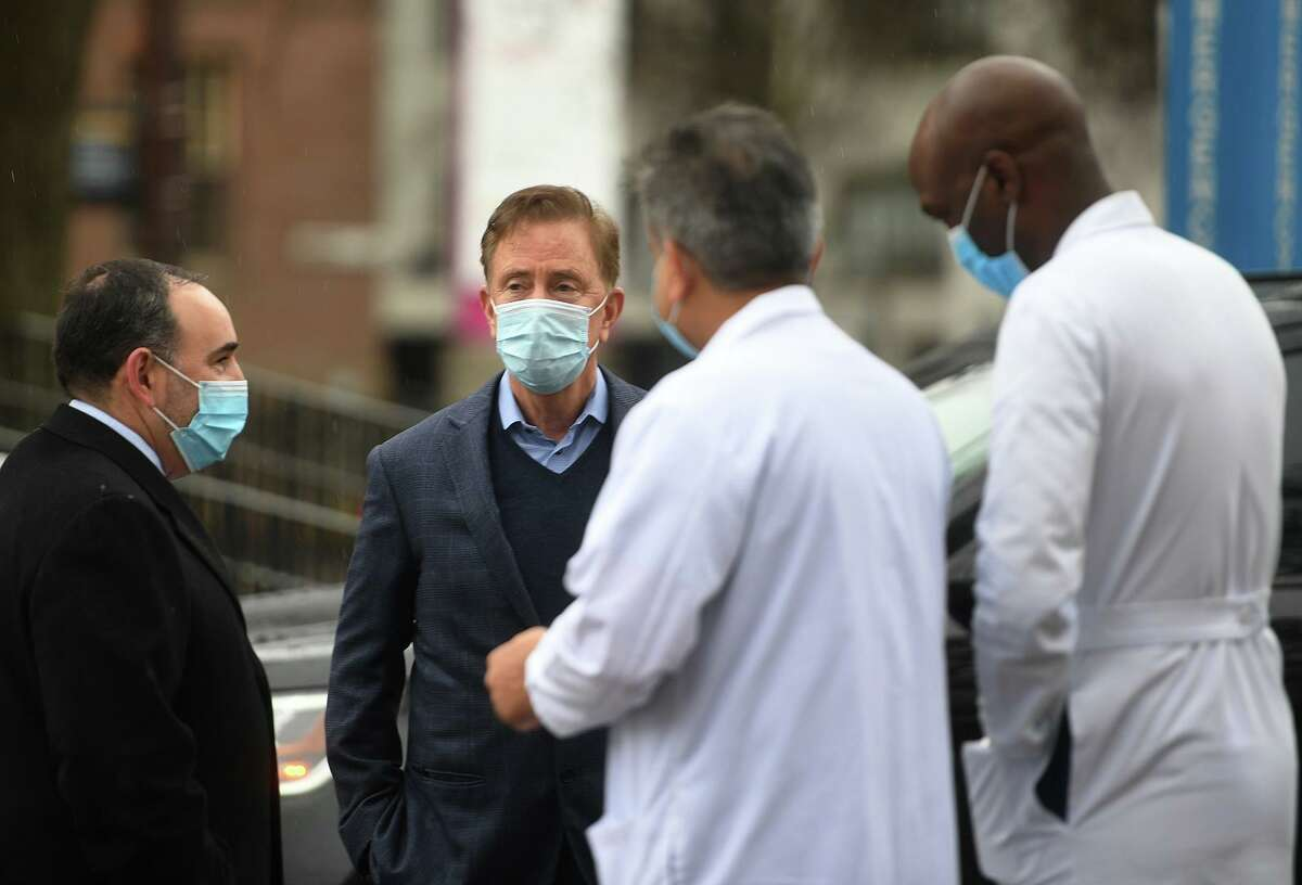 Governor Ned Lamont, second from left; is greeted by Hartford Health Care staff including President and CEO Jeffrey A. Flaks, left, for the roll out of the initial doses of the Pfizer Covid-19 vaccine at Hartford Hospital in Hartford, Conn. on Monday, December 14, 2020.