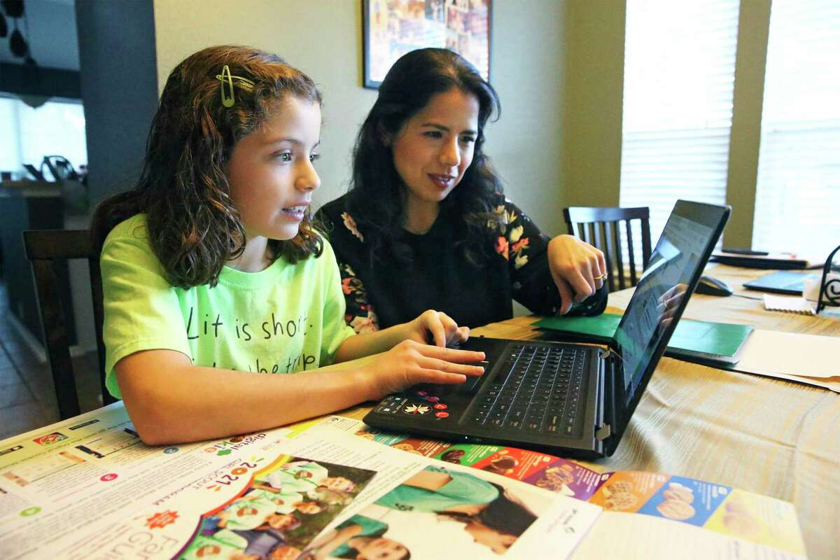 Girl Scout Emilia Williamson gets some assistance from her mother Melissa Vela-Williamson in setting up her online platform for selling cookies as the Girl Scouts of Southwest Texas begin online sales Monday.