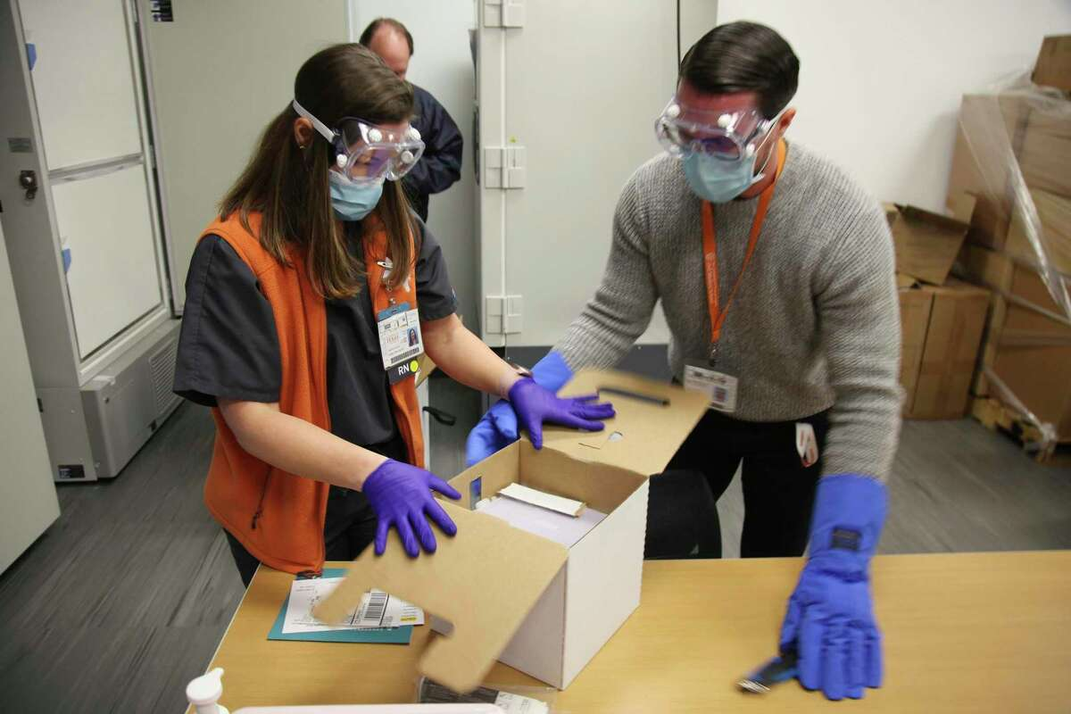 Jennifer Harrison, senior director of clinical operations at the University of Texas Health Austin Dell Medical School, and Devin Kline, materials manager open the first shipment of Pfizer-BioNTech COVID-19 vaccines to arrive at the hospital in Austin, Texas on Monday Dec.14, 2020. A growing chorus of education leaders and elected officials are calling on the state to give them priority to be vaccinated. (AP Photo/John L. Mone)