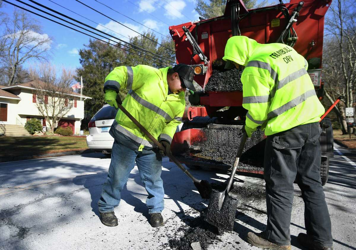 A Trumbull Public Works crew utilizes the town's new hot box to fill potholes with heated patching material on Lake Avenue in Trumbull, Conn. on Wednesday, January 30, 2019.