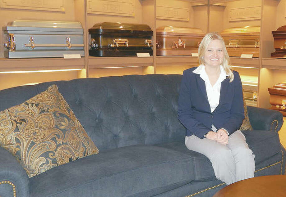 Tabitha Brown, a funeral director and embalmer with Airsman-Hires Funeral Homes, sits in the display room at Williamson Funeral Home in Jacksonville. Having a front row seat to the harm done by the COVID-19 pandemic can be tough, but being unable to offer a comforting touch to a grieving family member is tougher, funeral directors say. Photo: Angela Bauer | Journal-Courier