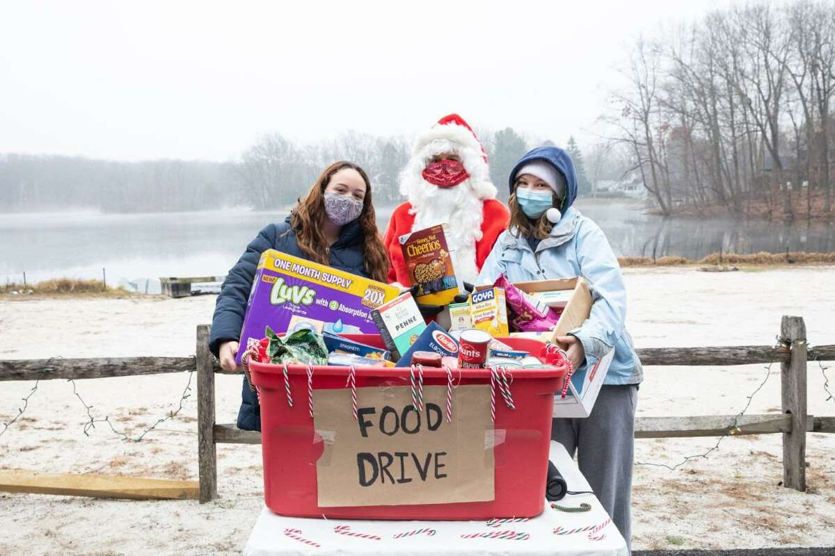 Santa visits Twixt Hills Road in Ridgefield on Saturday, Dec. 12 for a drive-thru holiday party. There was a mailbox for children to drop off their wish list for Santa, a food drive by Ridgefield High School seniors Kiralyse Hermann and Olivia Clausen, and a gift for each child. Pictured are: Hermann, Goldenberg and Clausen.