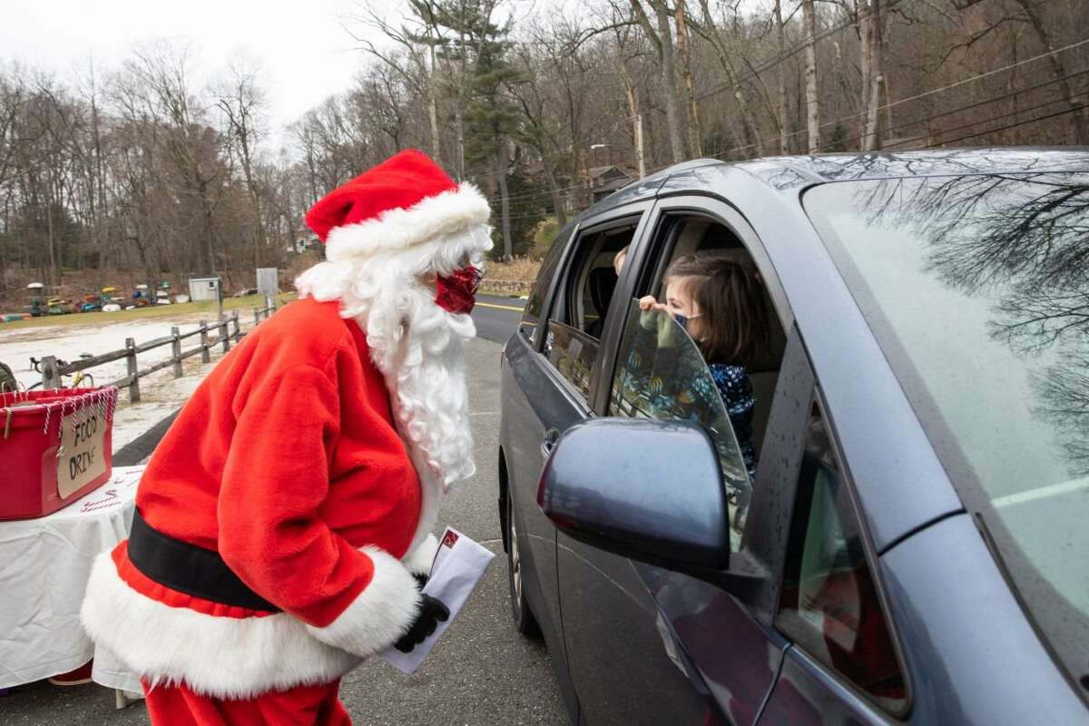 Santa visits Sloan Scott and Dave Goldenberg for a drive-thru holiday party on Twixt Hills Road on Saturday, Dec. 12 where there was also a mailbox for children to drop off their wish list for Santa, a food drive held by Ridgefield High School seniors Kiralyse Hermann, and Olivia Clausen, (pictured in the photo before this one), and a gift for each child.