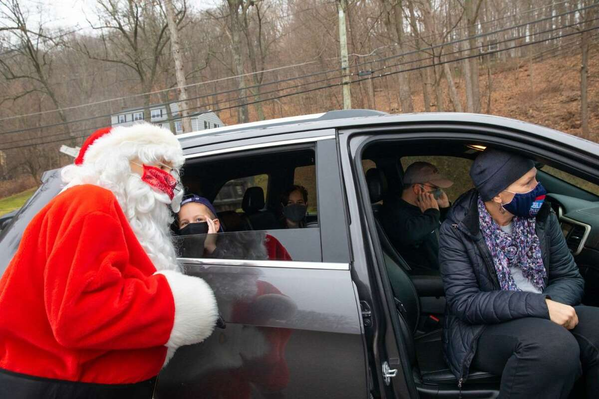 Parents Christine and Dave Balog try not to listen to their son, Mason Balog, telling Santa what he wants for Christmas during a drive-thru holiday party on Twixt Hills Road on Saturday, Dec. 12 where there was also a mailbox for children to drop off their wish list to Santa, a food drive held by Ridgefield High School seniors Kiralyse Hermann, and Olivia Clausen, (pictured in a previous photo), and a gift for each child. Mason's sister in the background is Sienna Balog. Pictured are: Dave Goldenberg, Mason Balog, Christine Balog, Dave Balog, and Sienna Balog.