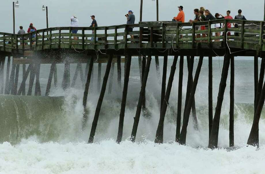 KILL DEVIL HILLS, NC - SEPTEMBER 03:  People stand on the Avalon Fishing Pier watching heavy surf caused by hurricane Earl, on September 3, 2010 in Kill Devil Hills, North Carolina. Hurricane Earl caused heavy surf as it passed the Outer Banks early Friday morning causing minimal damage.  (Photo by Mark Wilson/Getty Images) Photo: Mark Wilson, Getty Images / 2010 Getty Images