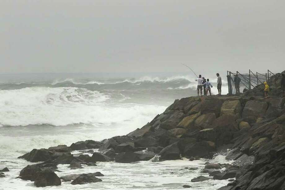MONTAUK, NY - SEPTEMBER 03: People watch the rough surf off the Montauk lighthouse on September 3, 2010 in Montauk, New York. Much of New England is preparing for Hurricane Earl, now a category 1 storm with sustained winds of 85 miles per hour. While current projections are that Earl will continue to weaken as it moves over cooler waters, it still described as a dangerous storm and the largest to make it into the New York City region since Hurricane Bob in 1991.  (Photo by Spencer Platt/Getty Images) Photo: Spencer Platt, Getty Images / 2010 Getty Images