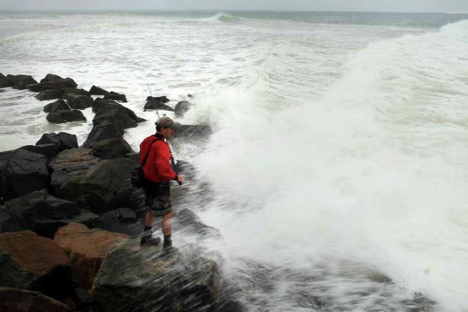 MONTAUK, NY - SEPTEMBER 03: A fisherman stands on the rocks in rough surf off the Montauk lighthouse on September 3, 2010 in Montauk, New York. Much of New England is preparing for Hurricane Earl, now a category 1 storm with sustained winds of 85 miles per hour. While current projections are that Earl will continue to weaken as it moves over cooler waters, it still described as a dangerous storm and the largest to make it into the New York City region since Hurricane Bob in 1991.  (Photo by Spencer Platt/Getty Images) Photo: Spencer Platt, Getty Images / 2010 Getty Images