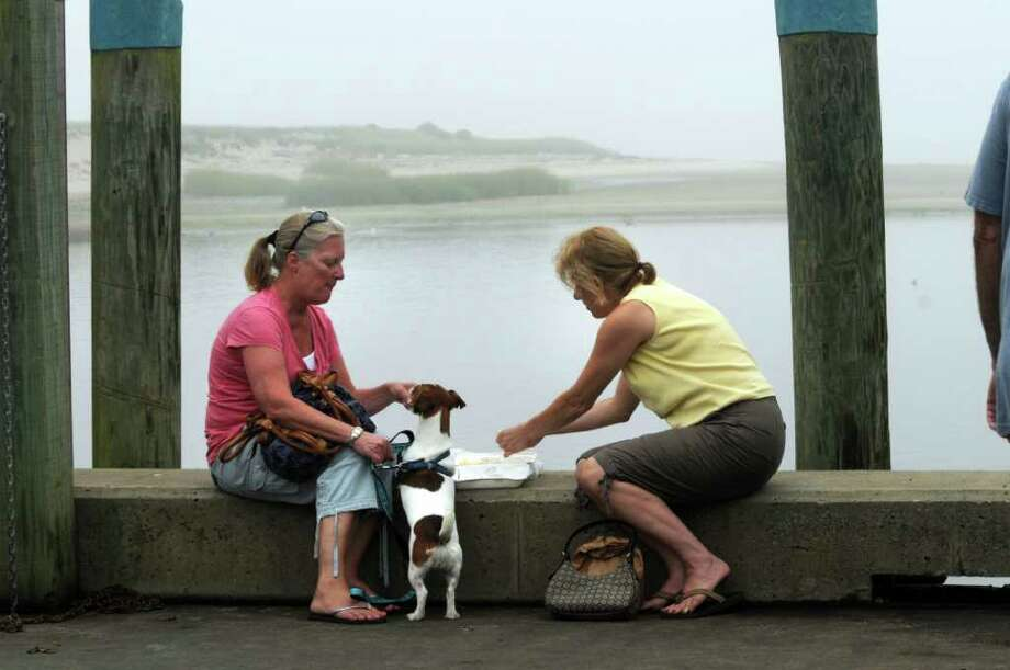 CHATHAM, MA -  SEPTEMBER 3:  New Jersey tourists Carol Olea (L) and Jill Rankin feed dog Ella Bella at the Chatham Fish Pier while waiting for Hurricane Earl to hit September 3, 2010 in Chatham, Massachusetts. Earl has been downgraded to a category 1 and is expected to pass off the Massachusetts coast near the outer islands late this evening, bringing high winds and rain. (Photo by Darren McCollester/Getty Images) *** Local Caption *** Jill Rankin;Carol Olea Photo: Darren McCollester, Getty Images / 2010 Getty Images