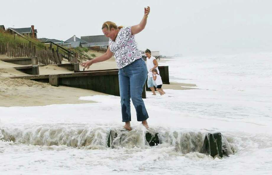 KILL DEVIL HILLS, NC - SEPTEMBER 03: A women gets surprised by incoming surf while standing on a jetty, on September 3, 2010 in Kill Devil Hills, North Carolina. Hurricane Earl caused heavy surf as it passed the Outer Banks early Friday morning causing minimal damage.  (Photo by Mark Wilson/Getty Images) Photo: Mark Wilson, Getty Images / 2010 Getty Images