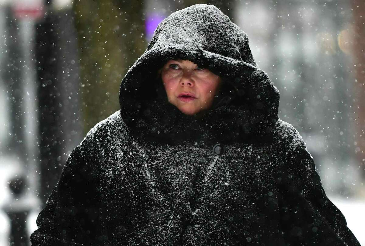 Pedestrians including Norwalk resident Karin McLean deal with the snow on North Main Street Saturday, Jan. 18, 2020, in Norwalk, Conn.