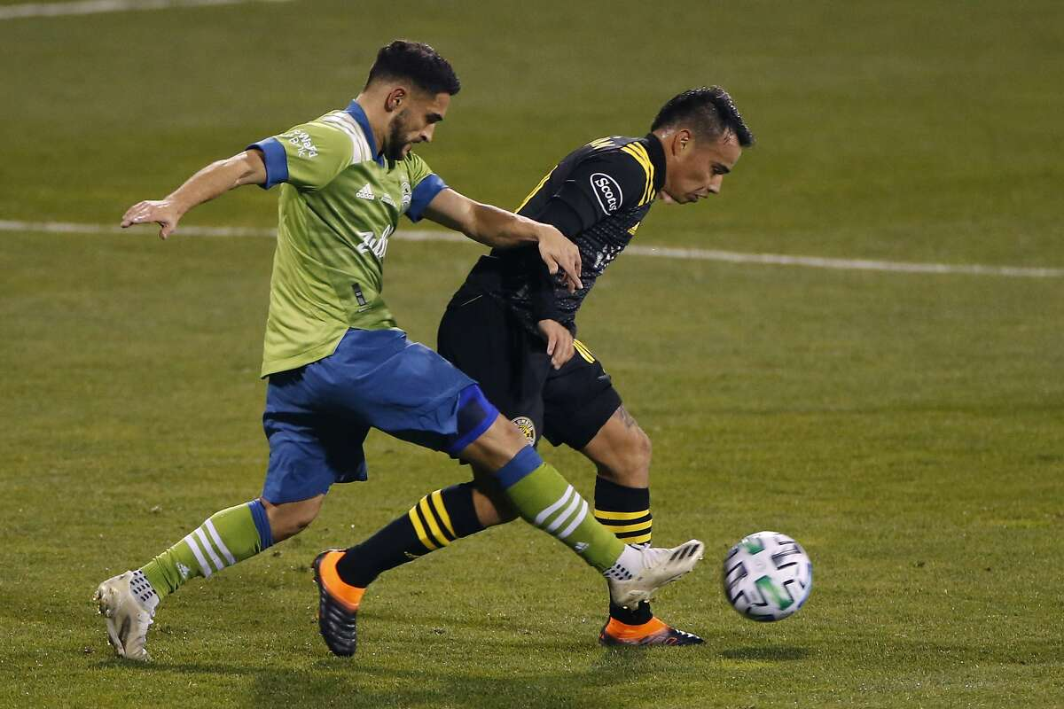 Seattle Sounders' Cristian Roldan, left, tries to dribble past Columbus Crew's Lucas Zelarayan during the first half of the MLS Cup championship soccer match Saturday, Dec. 12, 2020, in Columbus, Ohio. (AP Photo/Jay LaPrete)