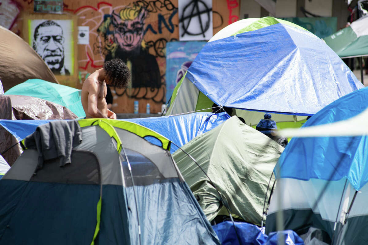 SEATTLE, WASHINGTON - JUNE 14: A protester stands at a campsite in Cal Anderson Park inside the âCapitol Hill Organized Protestâ formerly known as the âCapitol Hill Autonomous Zoneâ in Seattle, Washington on June 14, 2020. The âCapitol Hill Organized Protestâ was formed after Seattle Police abandoned its East Precinct during protests against police brutality and the death of George Floyd, an unarmed black man who died after being pinned down by a white police officer in Minneapolis, Minnesota, United States on May 25, 2020. (Photo by Noah Riffe/Anadolu Agency via Getty Images)