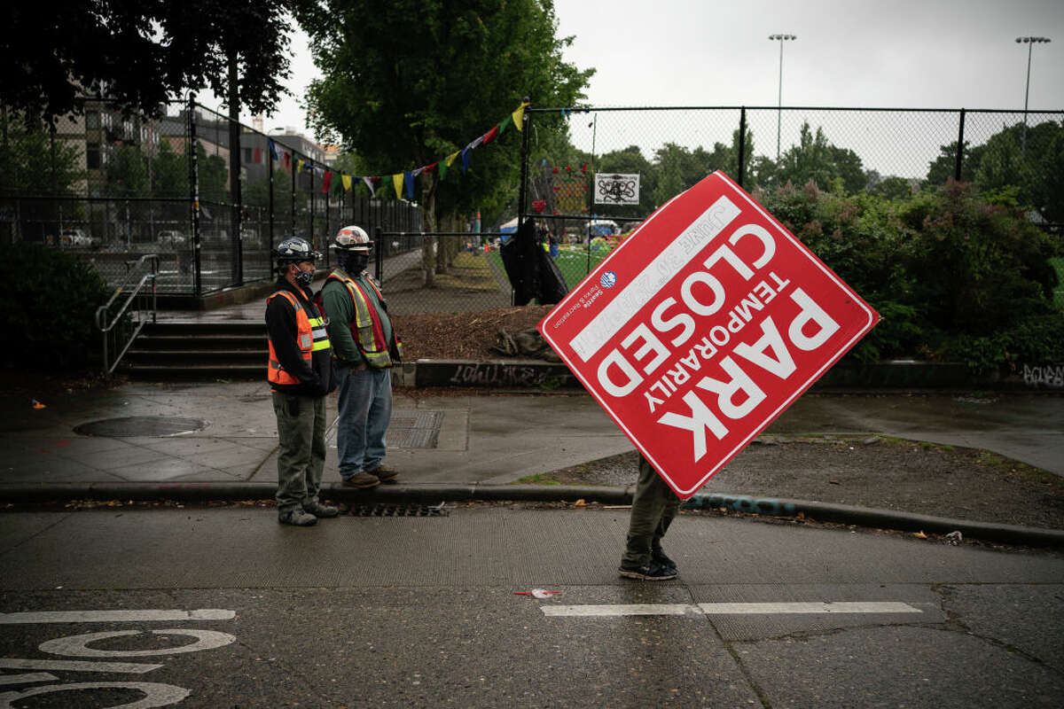 SEATTLE, WA - JUNE 30: A protester carries away a newly-placed park closure sign at an entrance to the Capitol Hill Organized Protest (CHOP) zone on June 30, 2020 in Seattle, Washington.