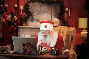 Santa Claus using a computer in his house to do a Christmas video conference. He is typing his present list on the red mobile phone.