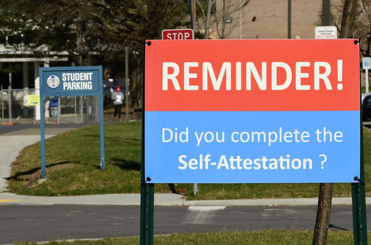 A reminder sign for completion of COVID-19 self-attestation is seen upon entering Shaker High School on Tuesday, Dec. 15, 2020 in Colonie, N.Y. More districts announced they are shifting entirely to remote learning until January. (Lori Van Buren/Times Union)