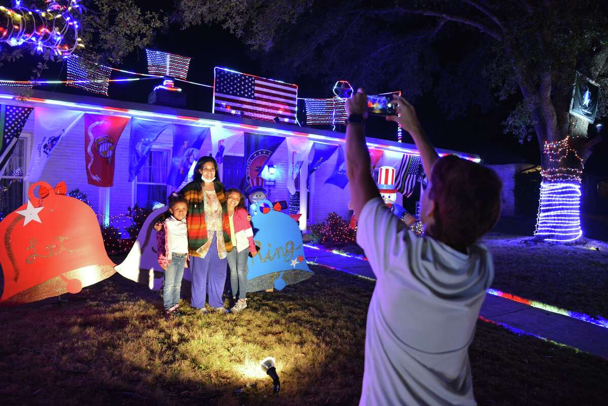 Jennifer Newman takes pictures of Sheila Meadows and her two children, Na'Leyah Mathis and Markaysia Shelton, in her front yard during Windcrest Light Up.