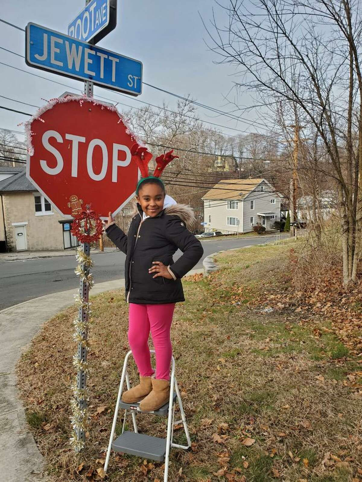 Morgan Hughes stands next to the stop sign she and her mother Keisha Martin-Velez decorated at the intersection of Jewett Street and Root Ave.