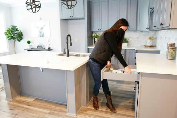Realtor Katie Day grabs flyers out of a drawer in a model home in a new development she is marketing in Houston.