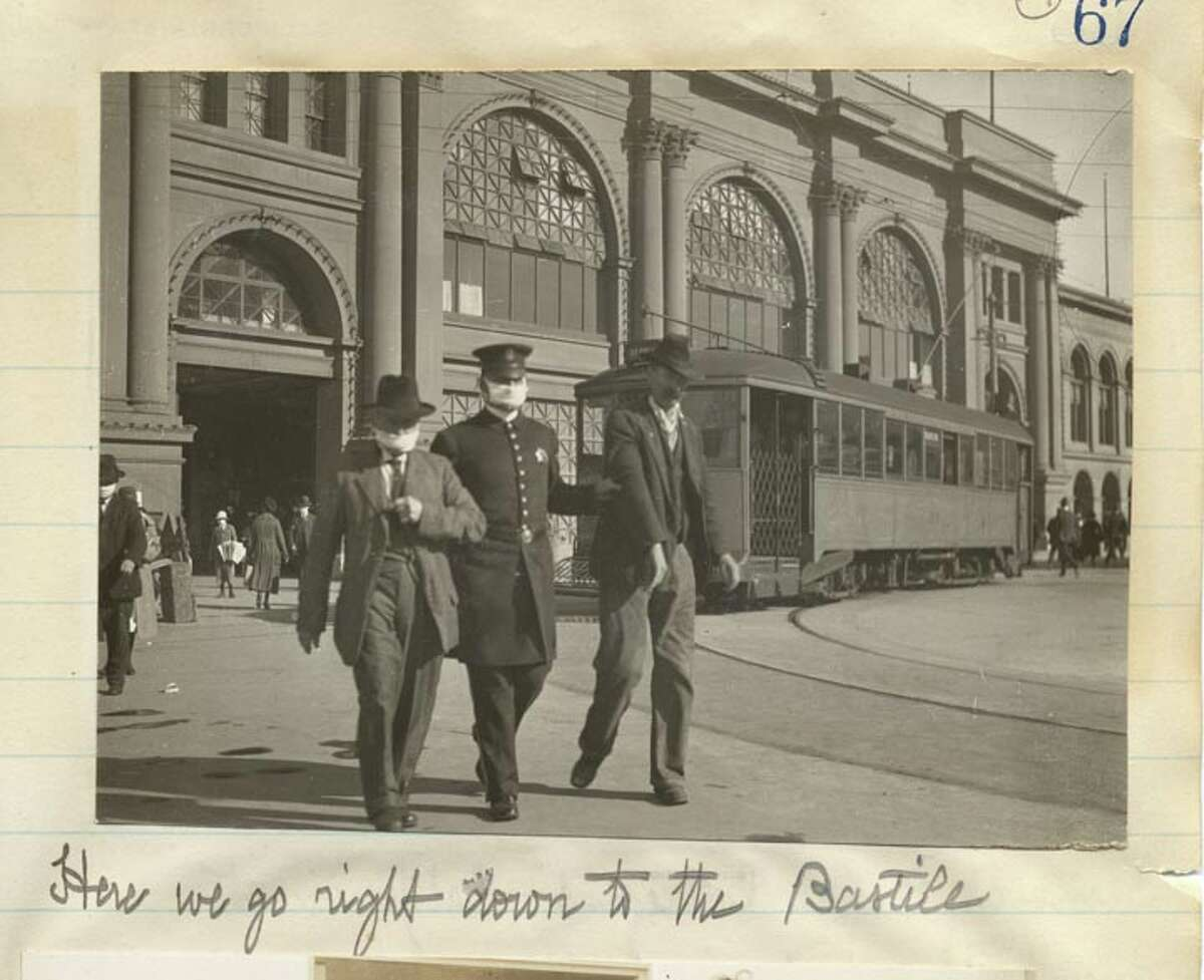 In this 1918 photo, a San Francisco police officer leads away two men, one of whom isn't wearing a mask, near the Ferry Building. The caption below the photo says,