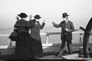A masked man pretends to hold up two masked women on San Francisco Bay in this 1918 photo, likely as a joke for resembling a bandit.  (Photo: OpenSFHistory / wnp14.13145.jpg)