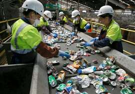 A team of workers sort aluminum cans near large bales of plastics ready for shipping away from the Recology recycling facility in San Francisco, Calif. on Thursday, Aug. 22, 2019.