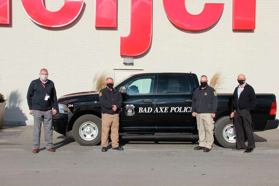 From left to right, Scott Neff, Jeff Rubin, David Rothe, and Alan Verstraete in front of the Bad Axe Meijer store. The two have partnered to give out Meijer gift cards to Bad Axe residents over the next week. (Robert Creenan/Huron Daily Tribune)