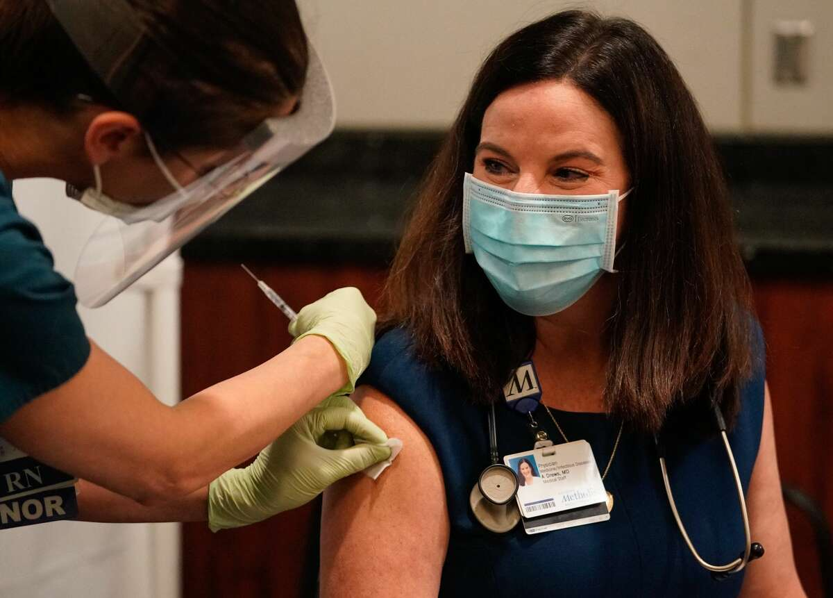 Houston Methodist Hospital RN Kristin Adolphs, left, prepares to give Dr. Ashley Drews the first COVID-19 vaccination at the hospital on Tuesday, Dec. 15, 2020 in Houston.