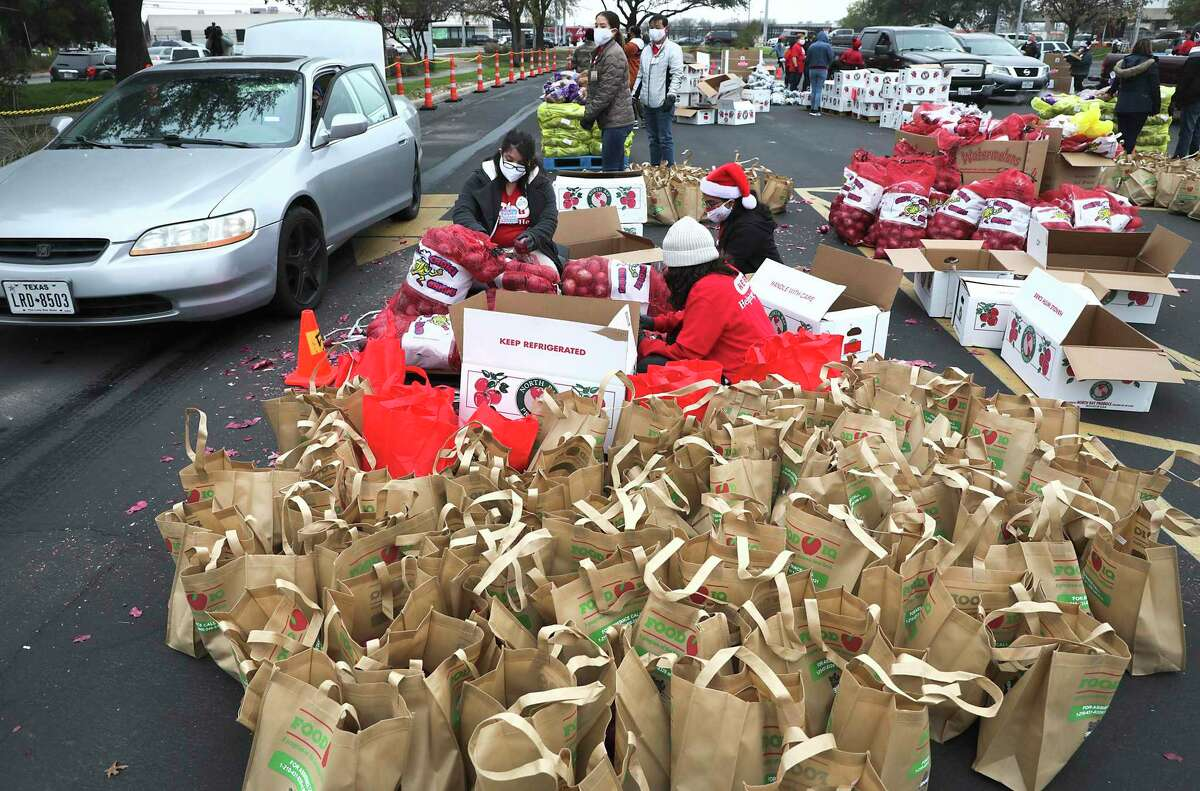 H-E-B workers assemble food bags as the San Antonio Food Bank holds its largest distribution of the year at the AT&T Center, on Tuesday, Dec. 15, 2020.