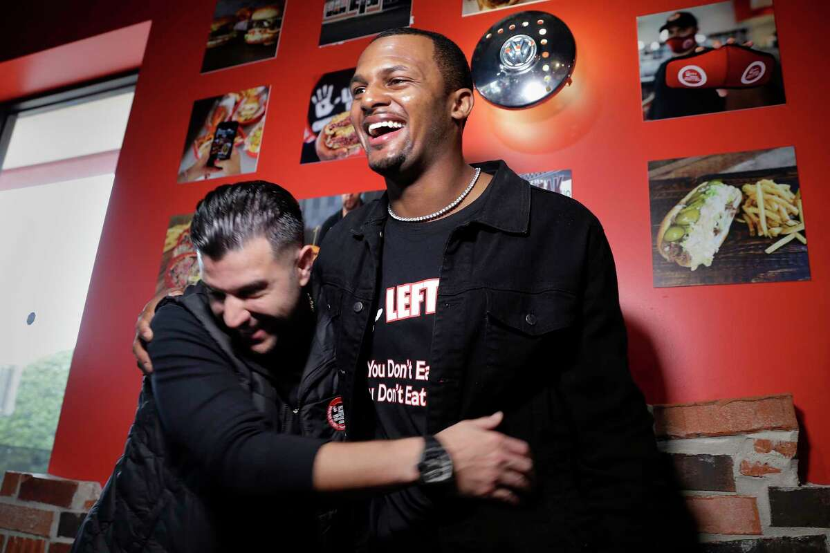 Sam Berry, left, Detroit based company founder, and Deshaun Watson, right, Texans quarterback and new restaurant owner hug as they speak during a press conference on the grand opening of the new Lefty's Cheesesteaks, Hoagies and Grill Tuesday, Dec. 15, 2020 near NRG Stadium in Houston, TX.