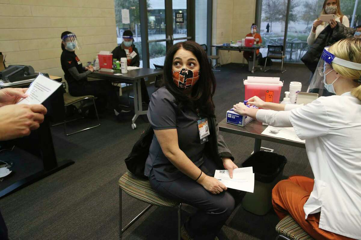 Stephanie Vasquez, PACU nurse with the UTHS ambulatory surgery center, gets instructions before getting the Pfizer COVID-19 vaccine at at Dell Medical School at US Austin in Austin, Tuesday, Dec. 15, 2020. Three hundred people were expected to get their first of two vaccines today.