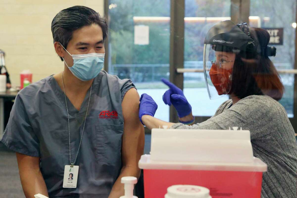 Department of Diagnostic Medicine assistant instructor Dr. Stephen Pan gets the Pfizer COVID-19 vaccine at Dell Medical School at UT Austin, Tuesday, Dec. 15, 2020. Three hundred people were expected to get their first of two vaccines today.