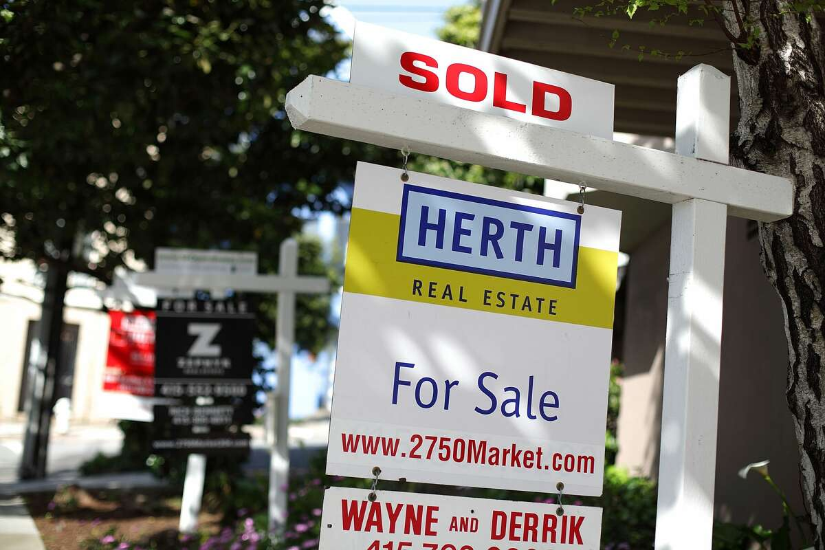 In this file photo, real estate signs are posted in front of homes for sale in San Francisco.