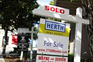 In this file photo, real estate signs are posted in front of homes for sale in San Francisco, California.