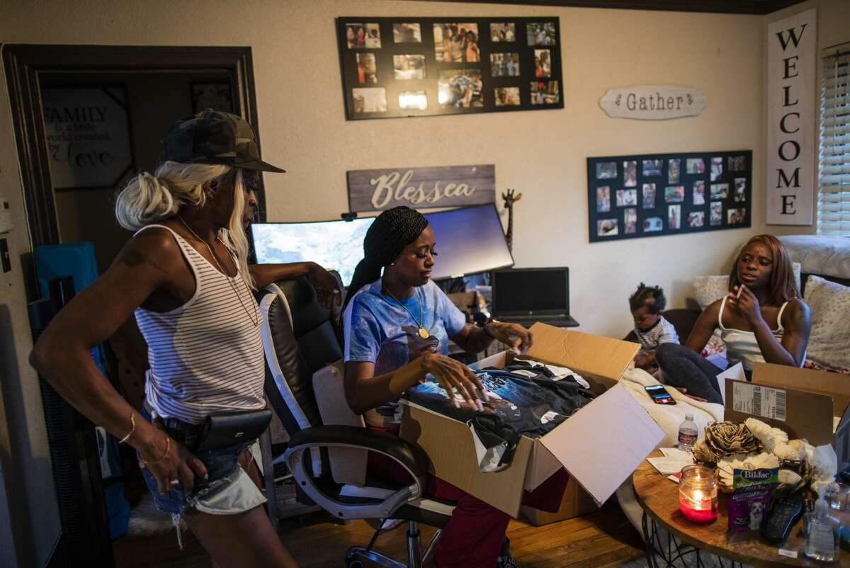 Jasmine Gray, center, 31, opens a box of custom memorial T-shirts with the photo of her deceased brother Chaz Jones during a family reunion Aug. 21, 2020, in Houston.