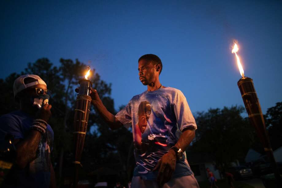 Andre Adams, 53, lights up a tiki torch at a birthday party in memory of his deceased cousin Aug. 21, 2020, in Houston. Photo: Marie D. De Jesús/Staff Photographer / © 2020 Houston Chronicle