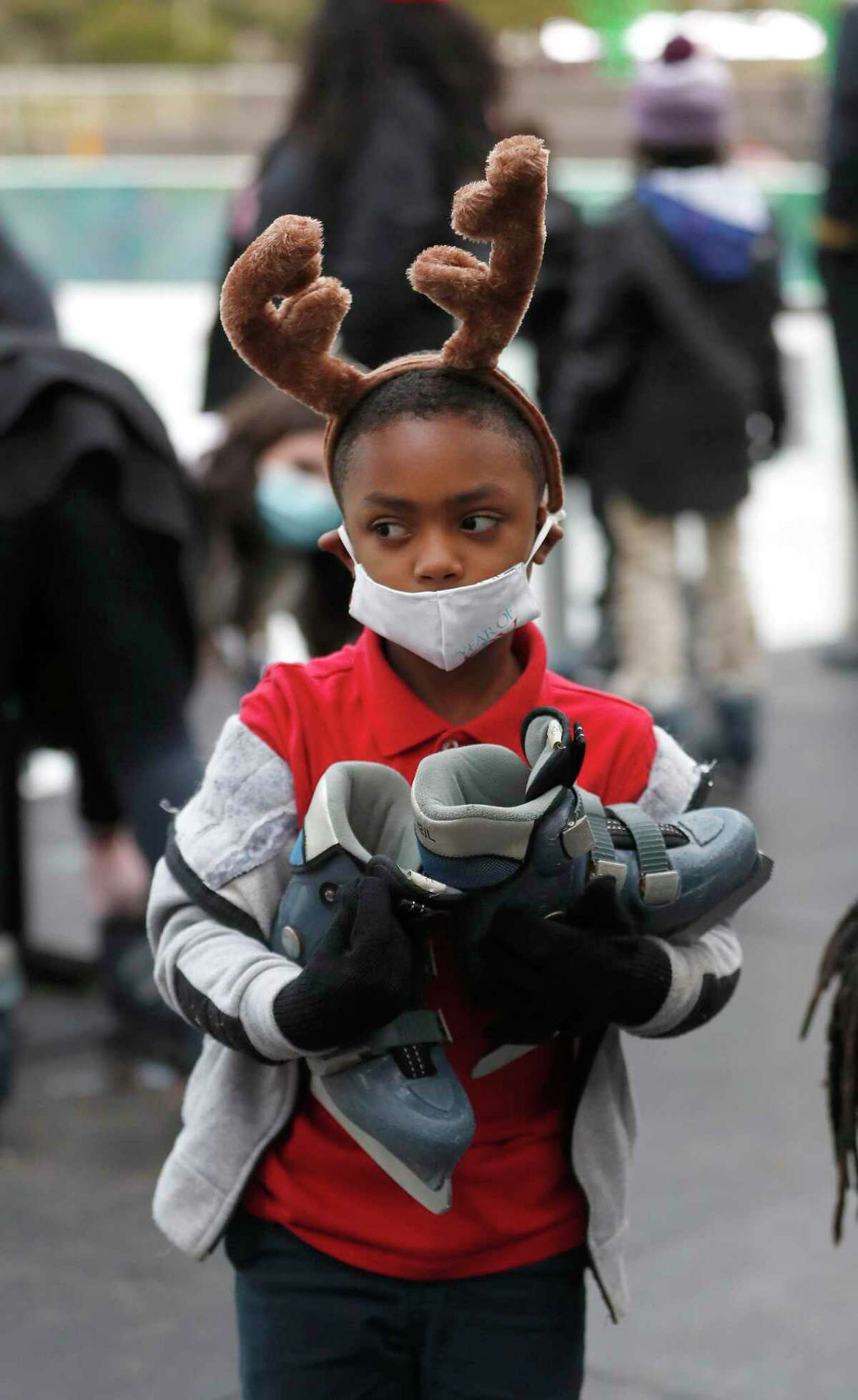 Kollyn Dugas, 5, center, carries his skates as he and other children from the Houston Southside Community Center skated during the 5th annual Year of Joy Holiday Ice Skating Party at Discovery Green.Monday, December 14, 2020, in Houston.
